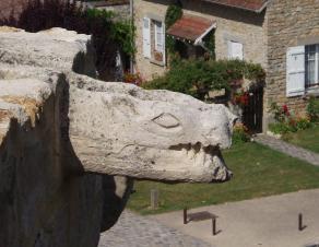 Sculpture d'une gargouille en hauteur à l'entrée du château