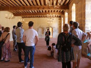 Des visiteurs adultes écoutent la guide dans la salle de l'Auditoire
