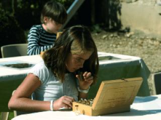 Photo représentant un enfant sentant une fiole de parfum
