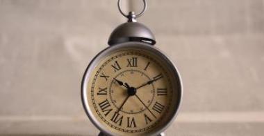 Photo représentant un réveil en métal avec les chiffres en romains
