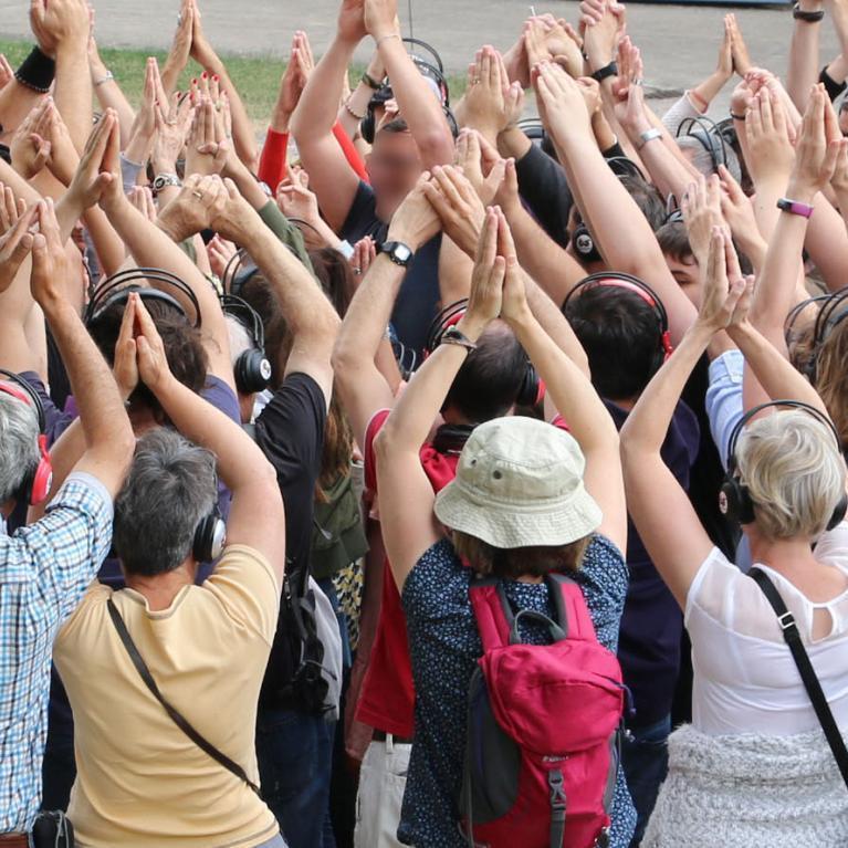 Les visiteurs lèvent les bras lors du final d'une visite décalée avec Magic Meeting