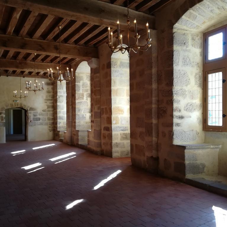 Intérieur de la grande salle du château avec fenêtres et coussièges sur la façade située à droite