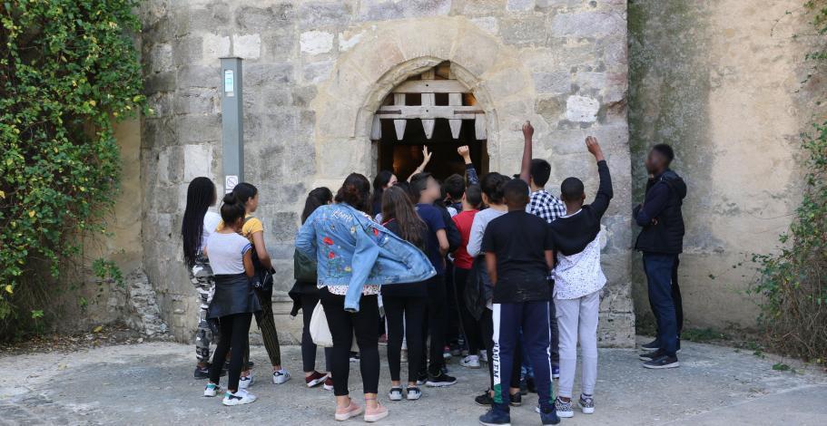 Un groupe de collégiens devant la herse du donjon de Blandy