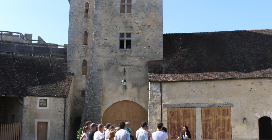 Un groupe de visiteurs suivent une visite guidée dans la cour du château